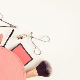 Top view of pink cosmetic bag consist of makeup brush, lipstick, brush on, scissors, mascara,  eyelash curler on white background - vintage filter tone